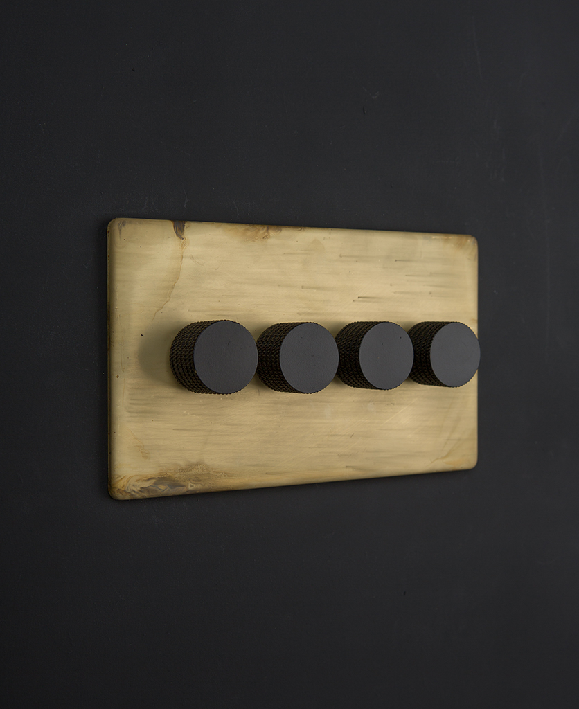 Smoked gold light dimmer switch with four black knurled dimming knobs