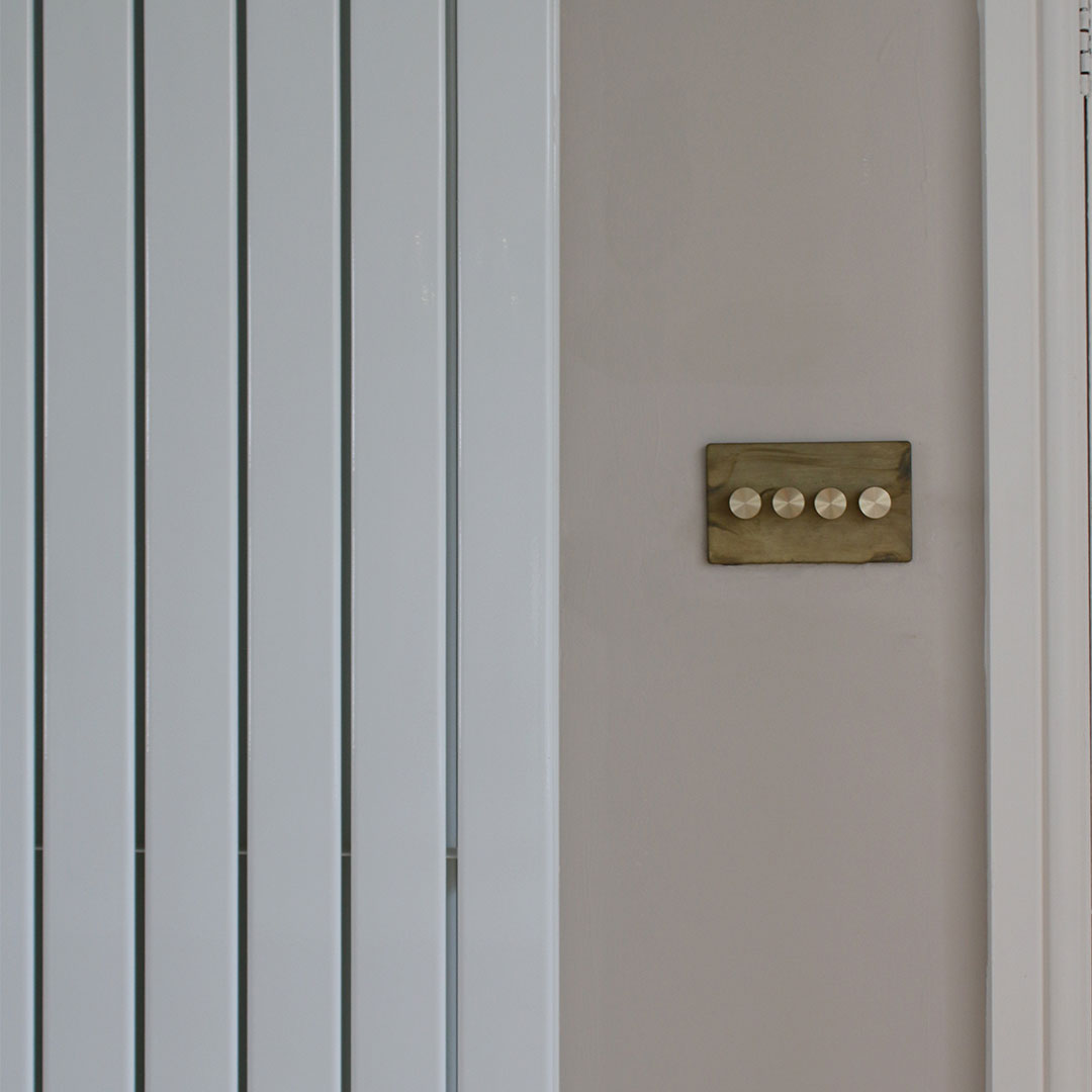 smoked gold quad dimmer with gold knobs against white background