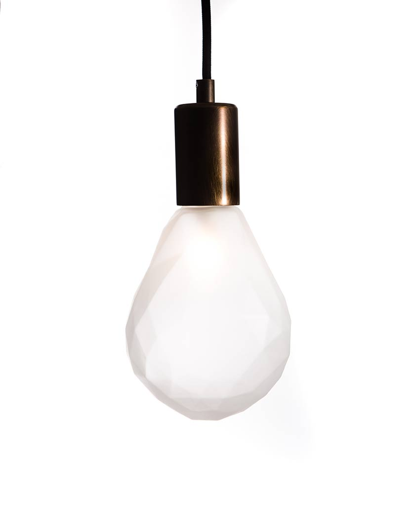 christalle frosted pear shaped geometric light bulb with brewer's brass bulb holder suspended from black fabric cable against white wall
