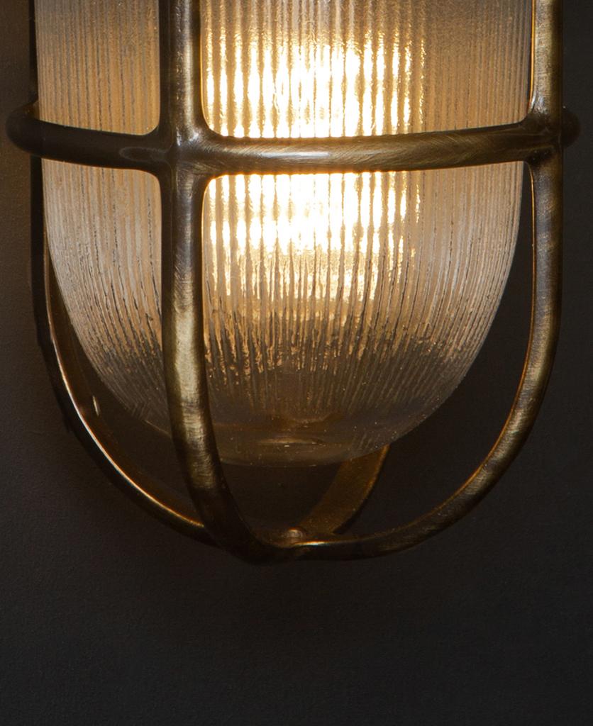 closeup of simon lit aged brass bulkhead light against black background