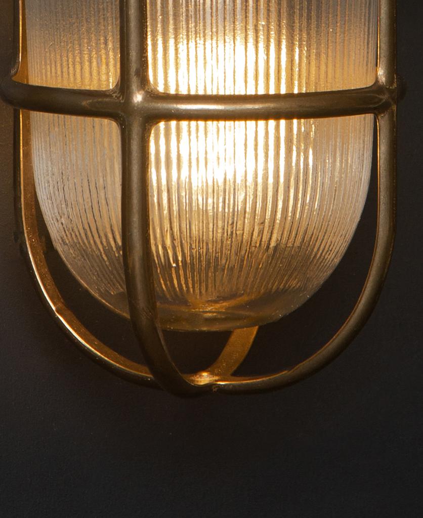 close up of lit brass simon exterior bulkhead lights against black background