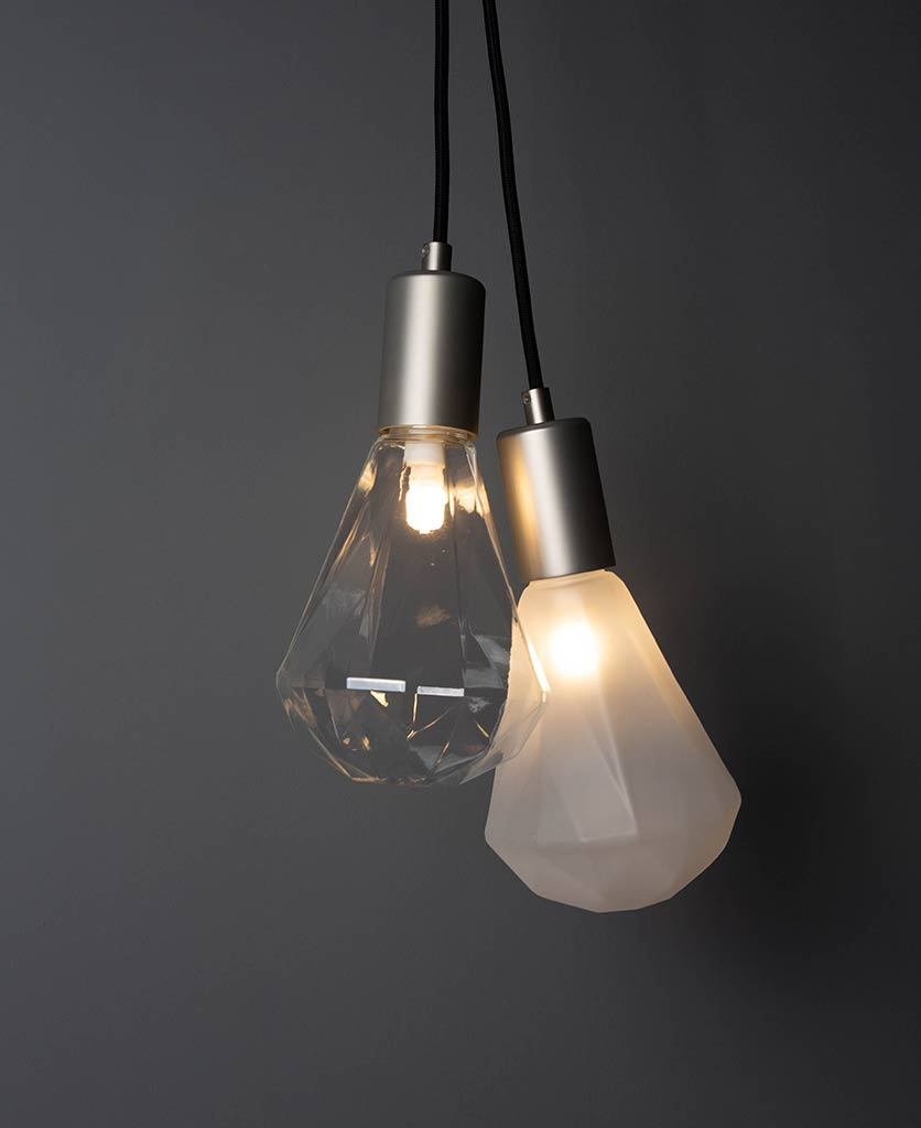 group shot of christalle glass pendant light one clear and one frosted with silver bulb holders againsta a dark grey wall
