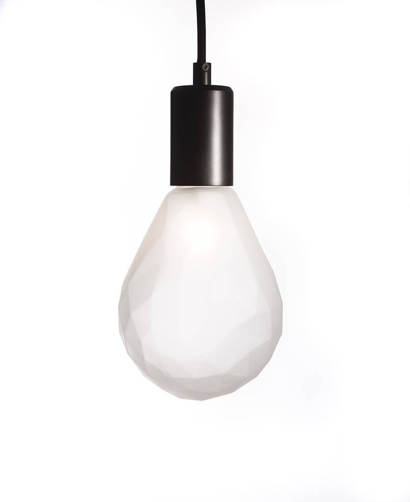 christalle frosted pear shaped geometric light bulb with bronze bulb holder suspended from black fabric cable against white wall