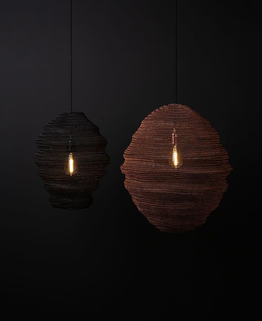 Copper mesh pendant light suspended against black background