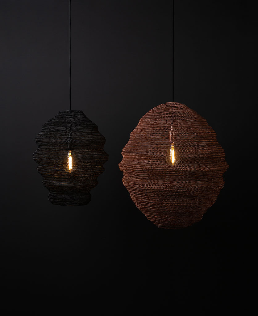 one copper mesh light and one black mesh light suspended from black fabric cable with lit bulbs against black wall