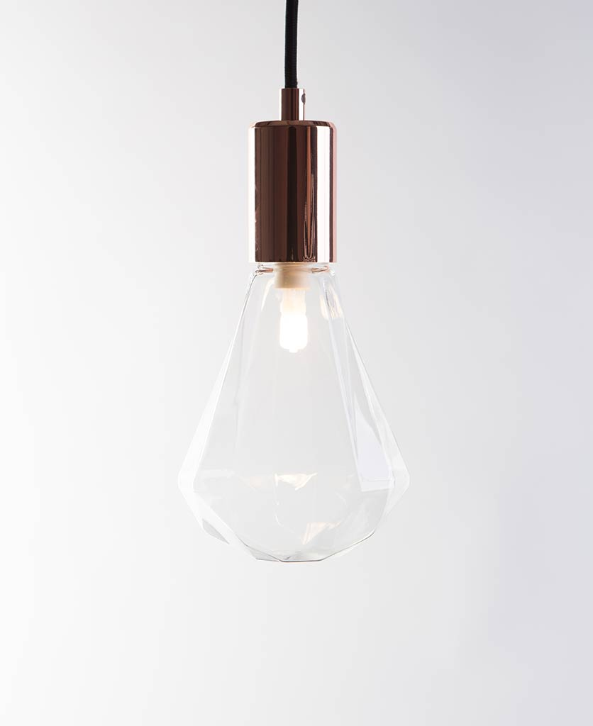 christalle glass pendant light diamond shaped geometric light bulb with polished copper bulb holder suspended from black fabric cable against white wall