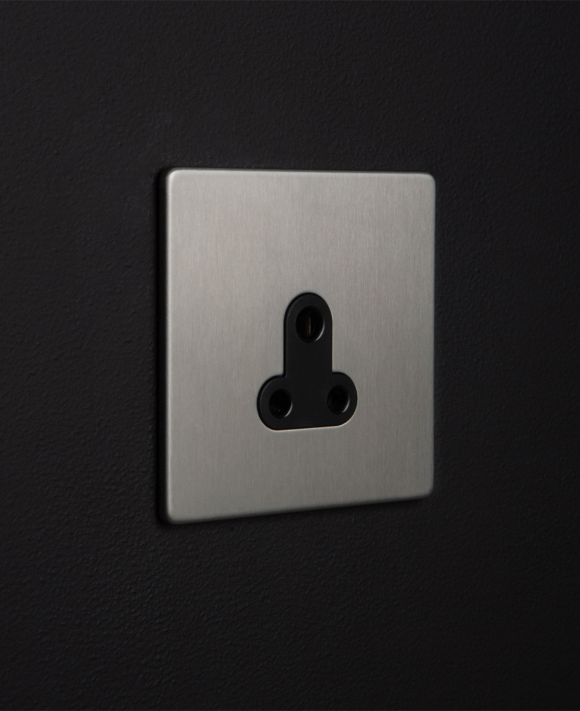 silver and black three pin socket against black background
