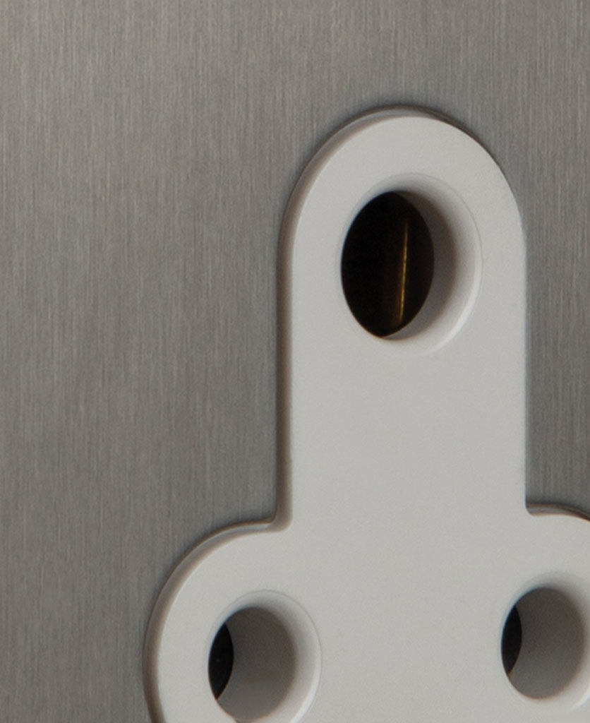 closeup of silver and white three pin socket