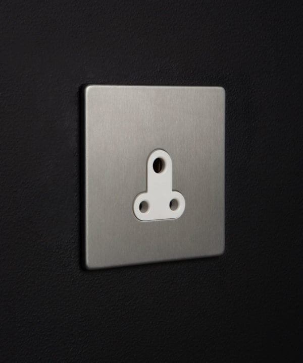 silver and white three pin socket against black background