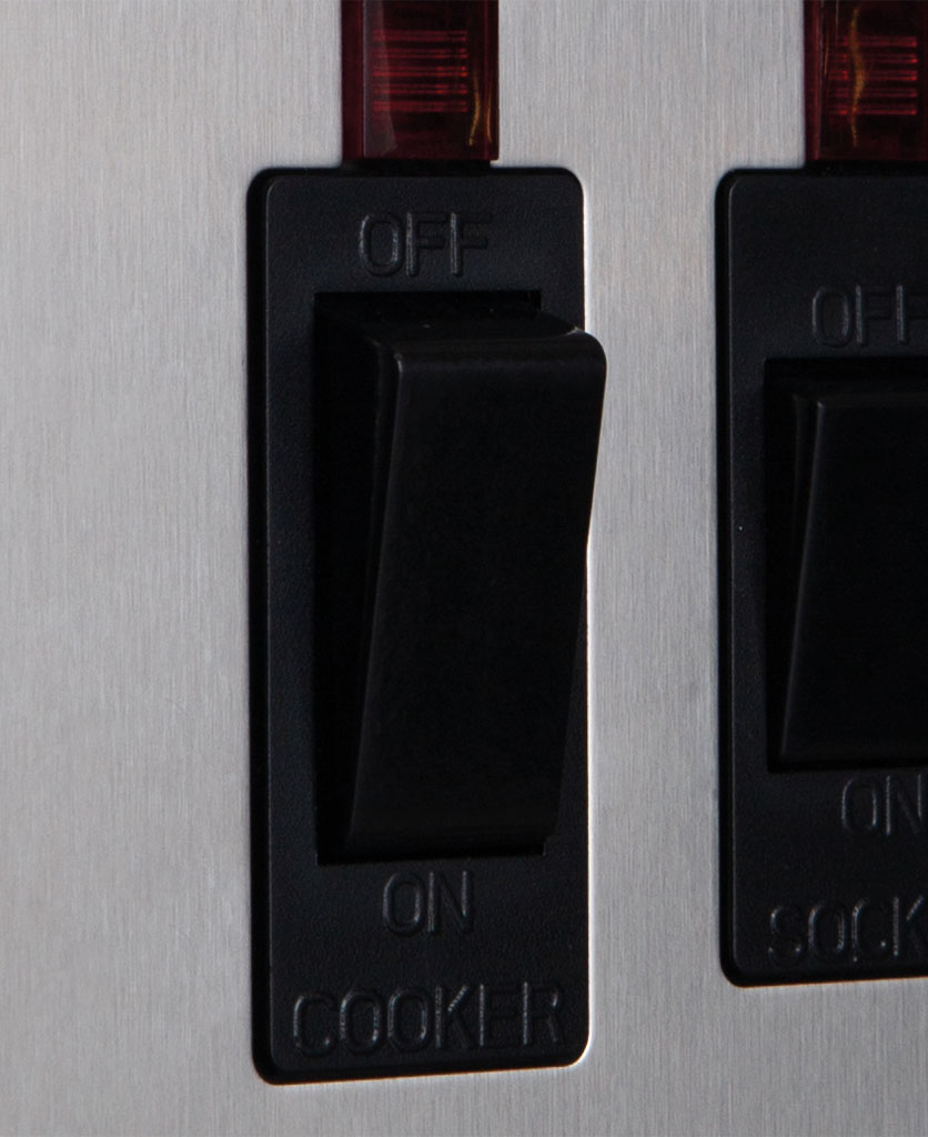 closeup of silver and black cooker switch with socket