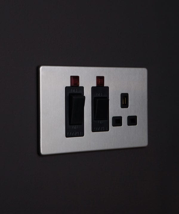 silver and black cooker switch with socket against black background