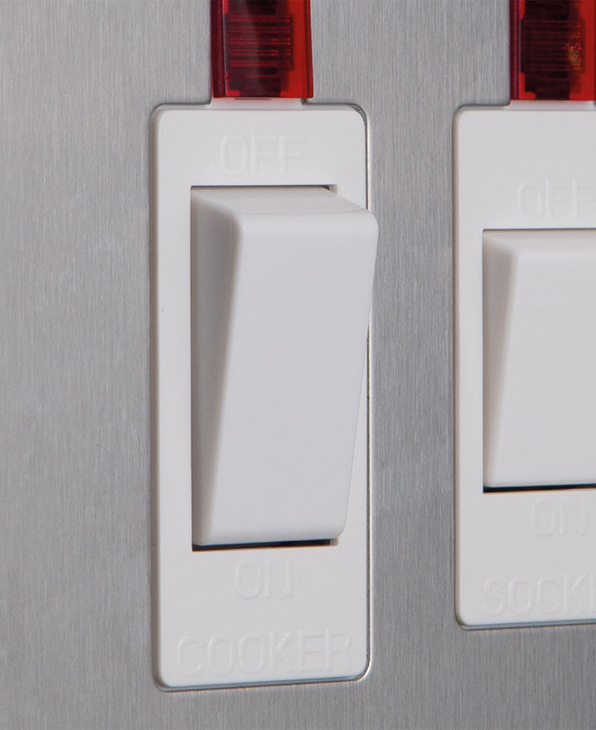 closeup of silver and white cooker switch with socket