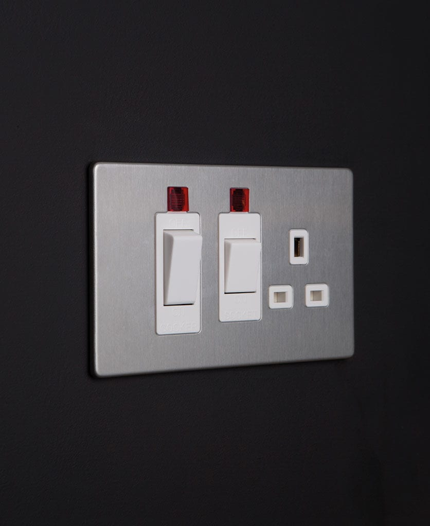 silver and white cooker switch and socket against black background