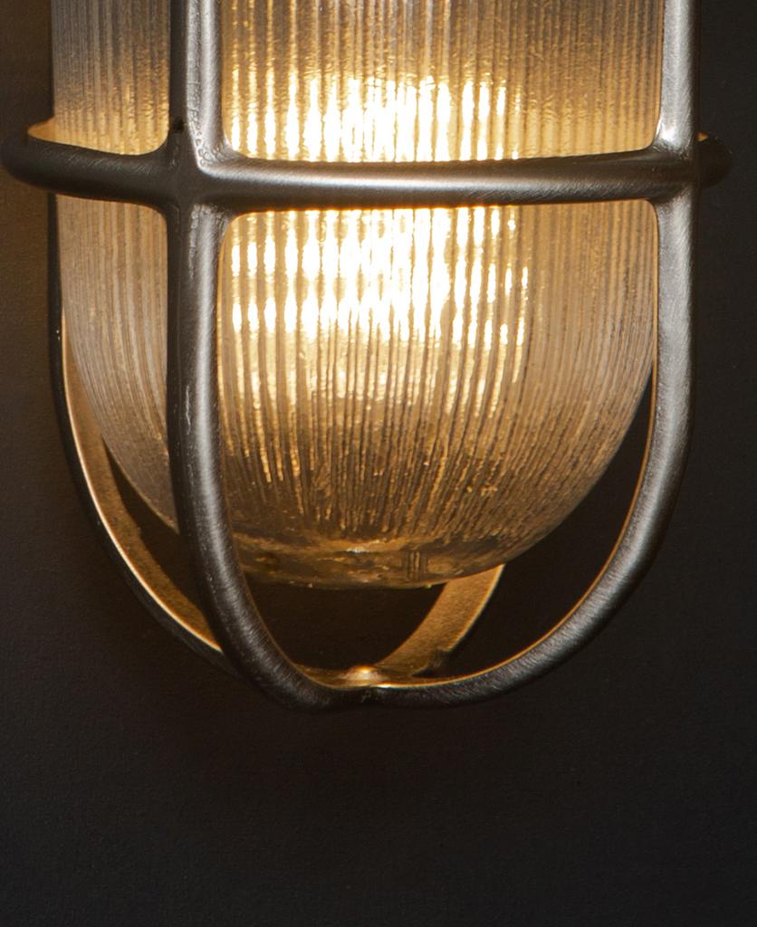closeup of lit simon silver bulkhead light against black background