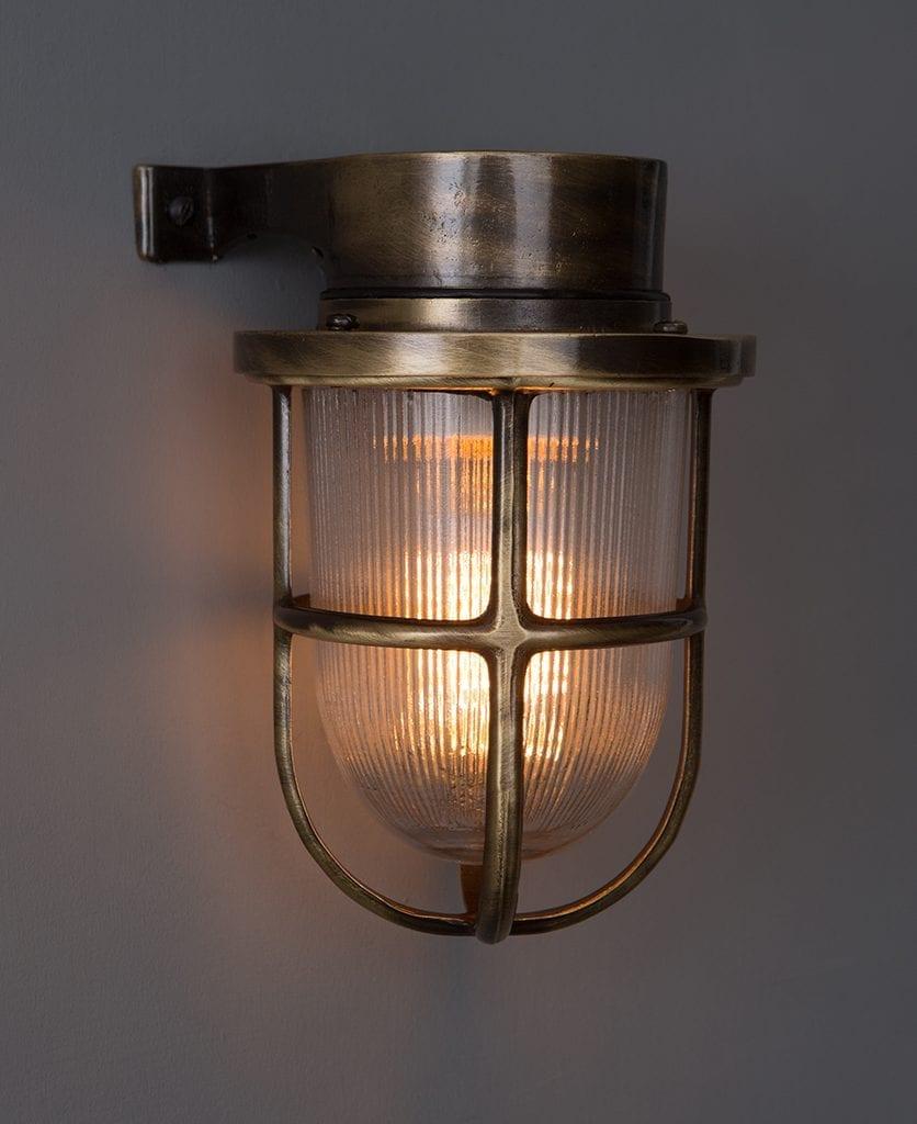 Simon aged brass bulkhead light against dark grey background