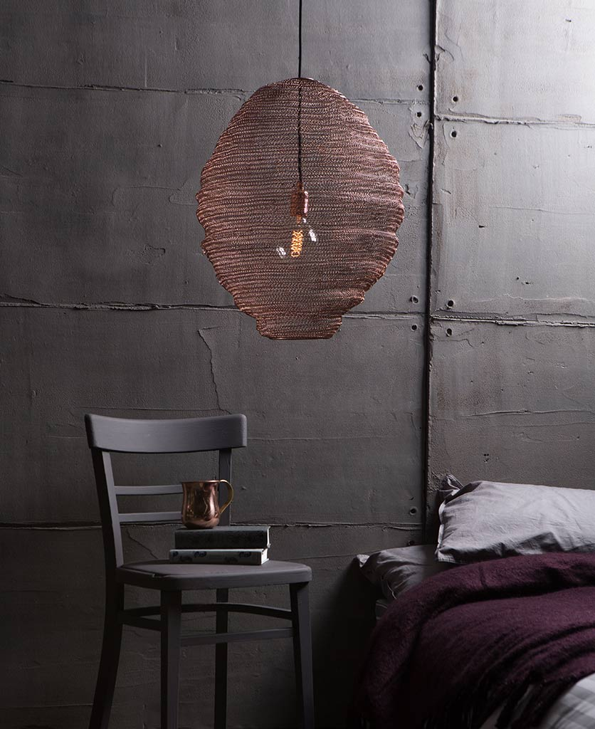 copper mesh pendant light suspended against a grey concrete wall above in a bedroom