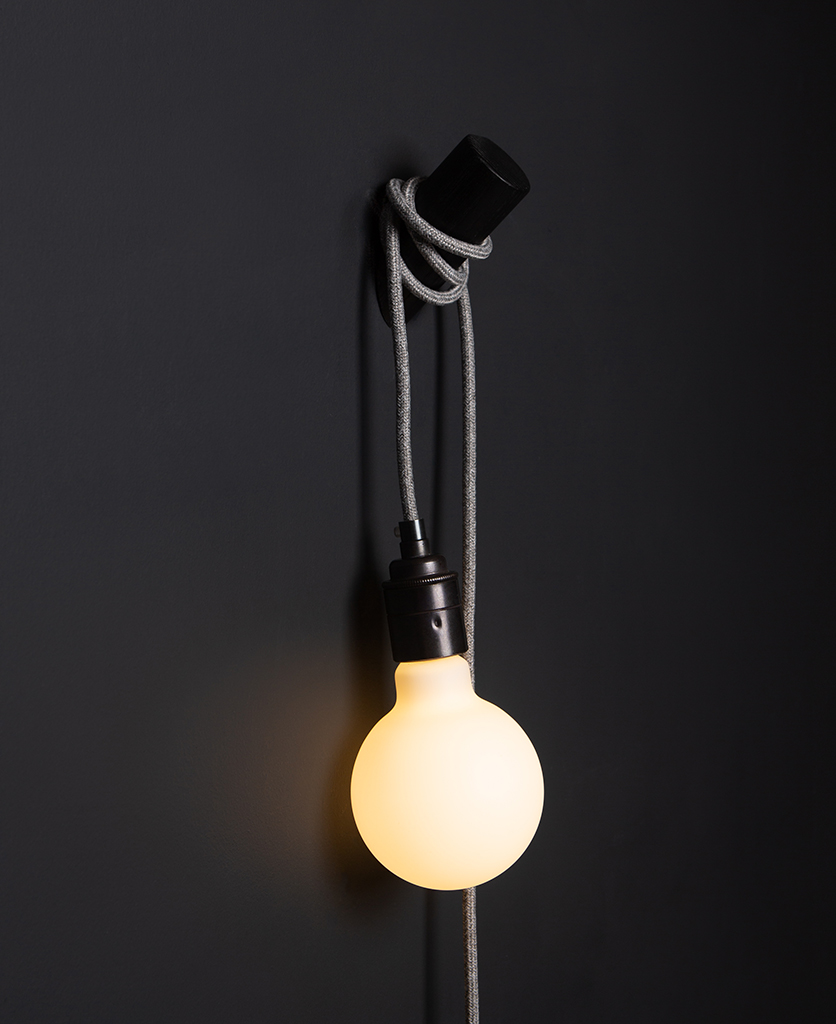 black peg lamp with grey jumper cable against black wall