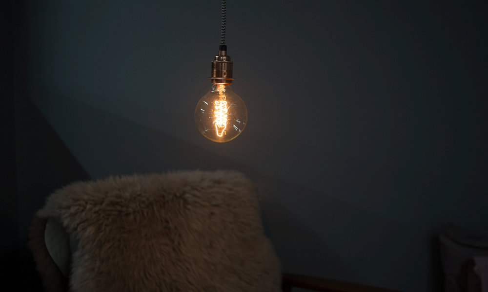 globe spiral filament bulb with silver bulb holder and black and white fabric cable against black background