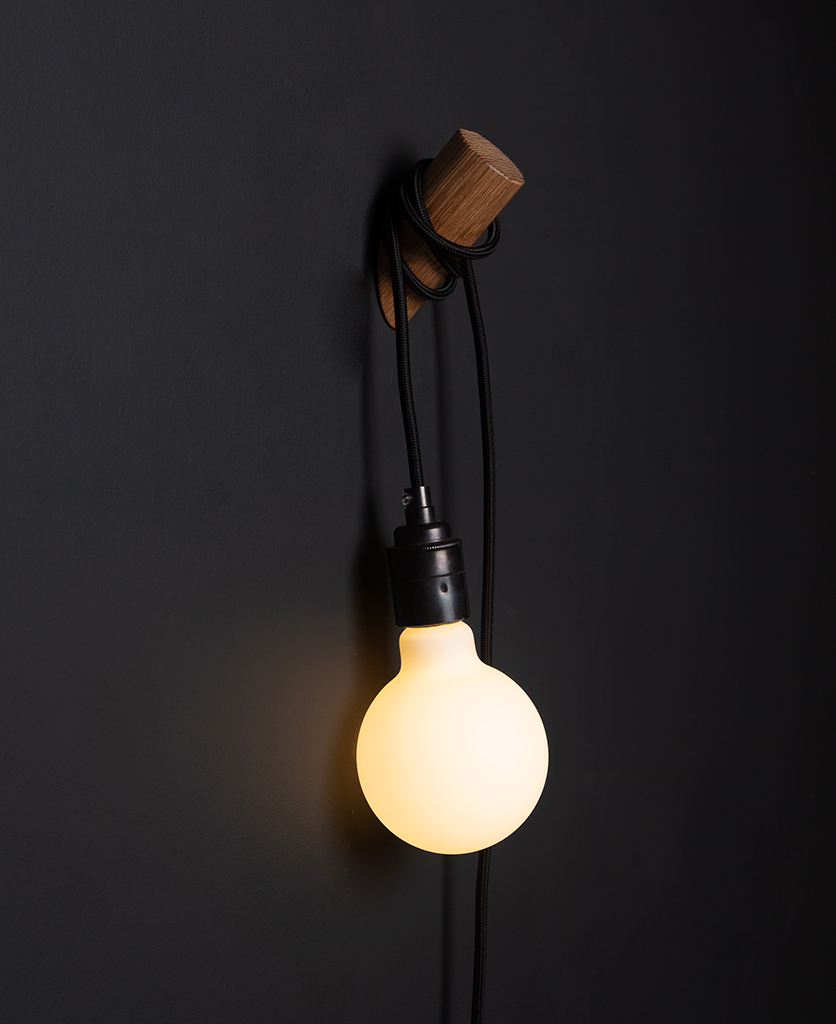 danish oil peg lamp with black cable on black wall