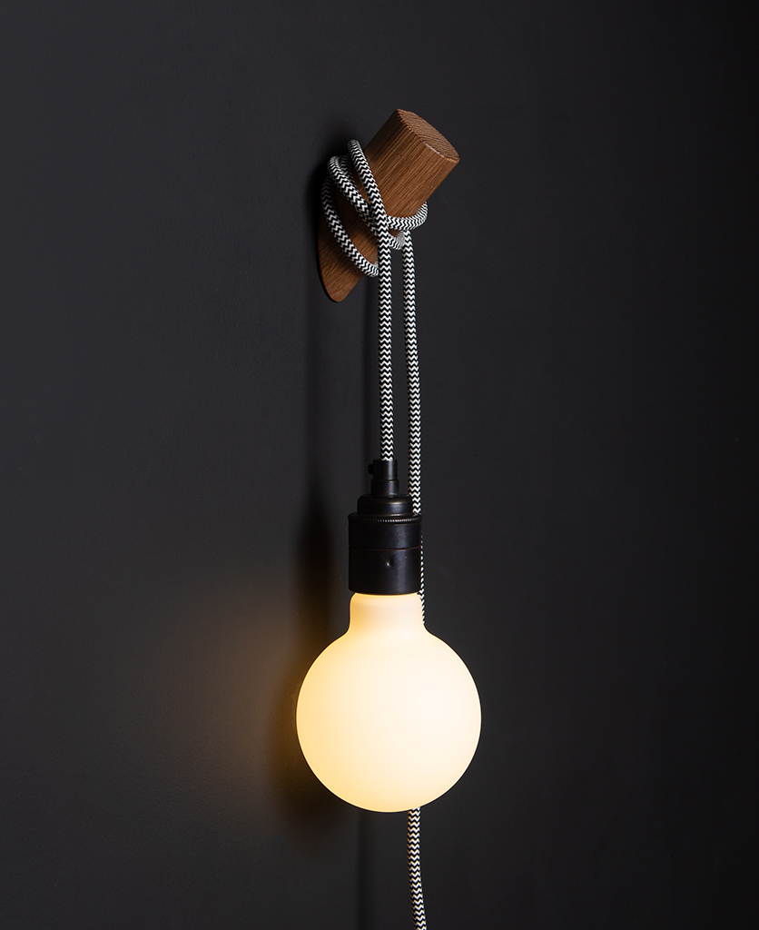 danish oil peg lamp with mint humbug cable against black wall