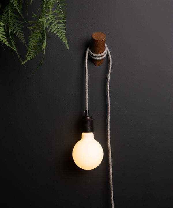 peg plug in wall lamp with dark oak peg and grey fabric cable against black wall