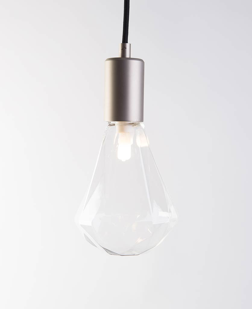 christalle glass pendant light diamond shaped geometric light bulb with dull nickel bulb holder suspended from black fabric cable against white wall