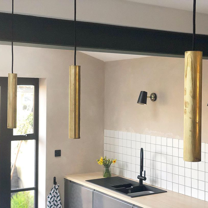 smoked gold baton pendant light suspended in a series in a white grey and neutral beige kitchen