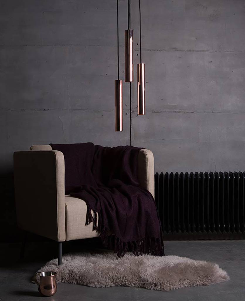 baton tube pendant lights suspended against a concrete wall next to an armchair