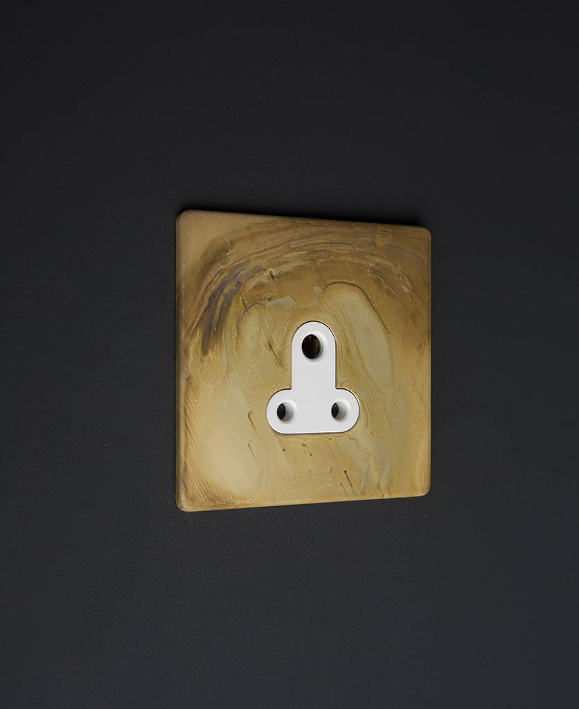 smoked gold & white three pin plug against black background