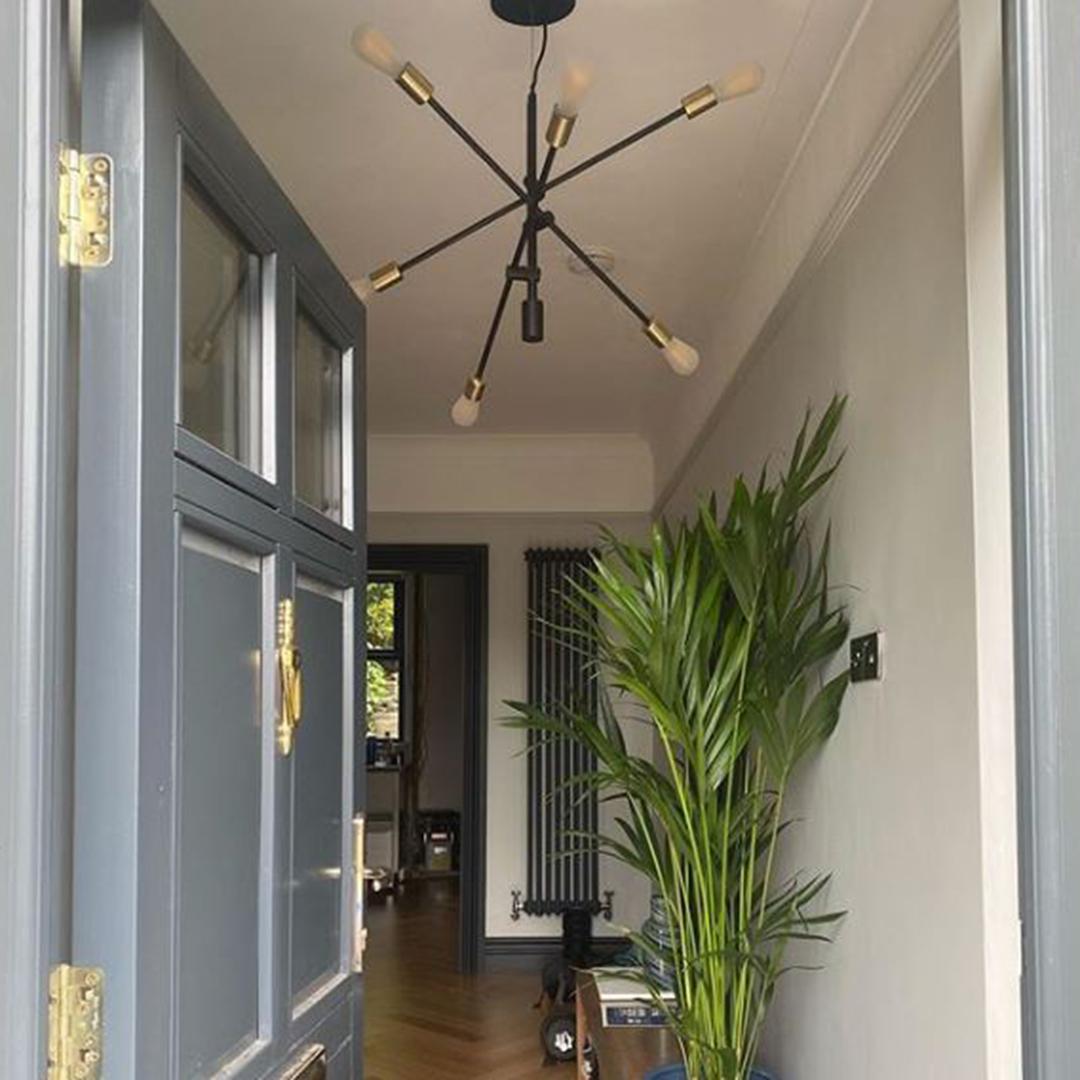 black trikonasana suspended in a light grey hallway