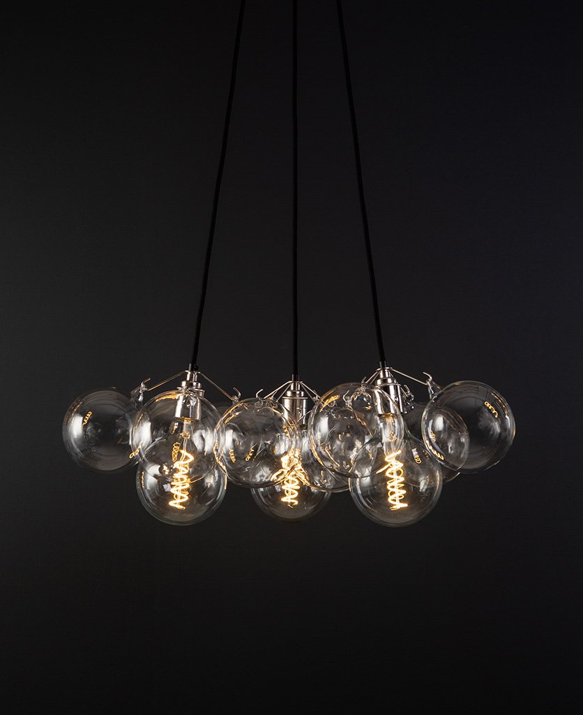 bubble pendant chandelier with 12 clear glass baubles and 3 silver bulb holders suspended from black fabric cable against a black wall