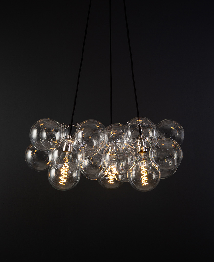 bubble pendant chandelier with 24 clear glass baubles and 3 silver bulb holders suspended from black fabric cable against a black wall