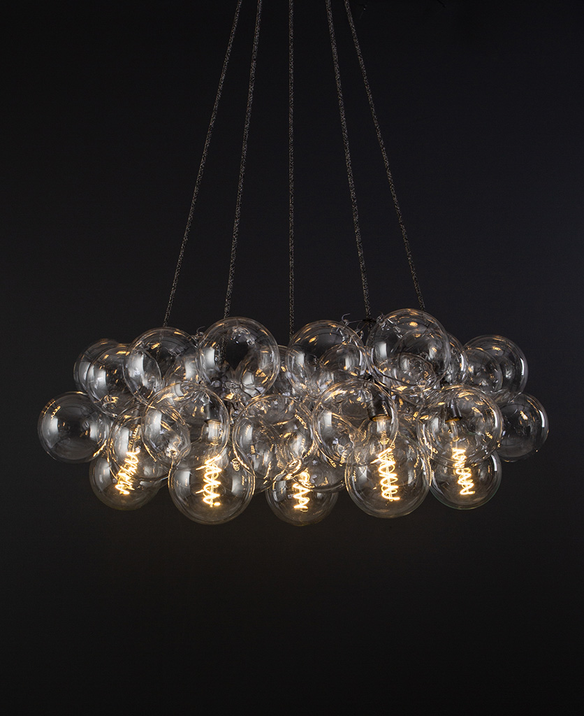 bubble glass chandelier with 40 glass baubles & 5 bronze bulb holders suspended from textured fabric cable against a black wall