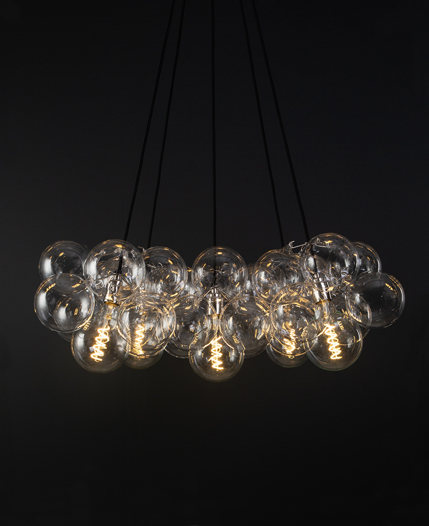 bubble glass chandelier with 40 glass baubles & 5 silver bulb holders suspended from black fabric cable against a black wall