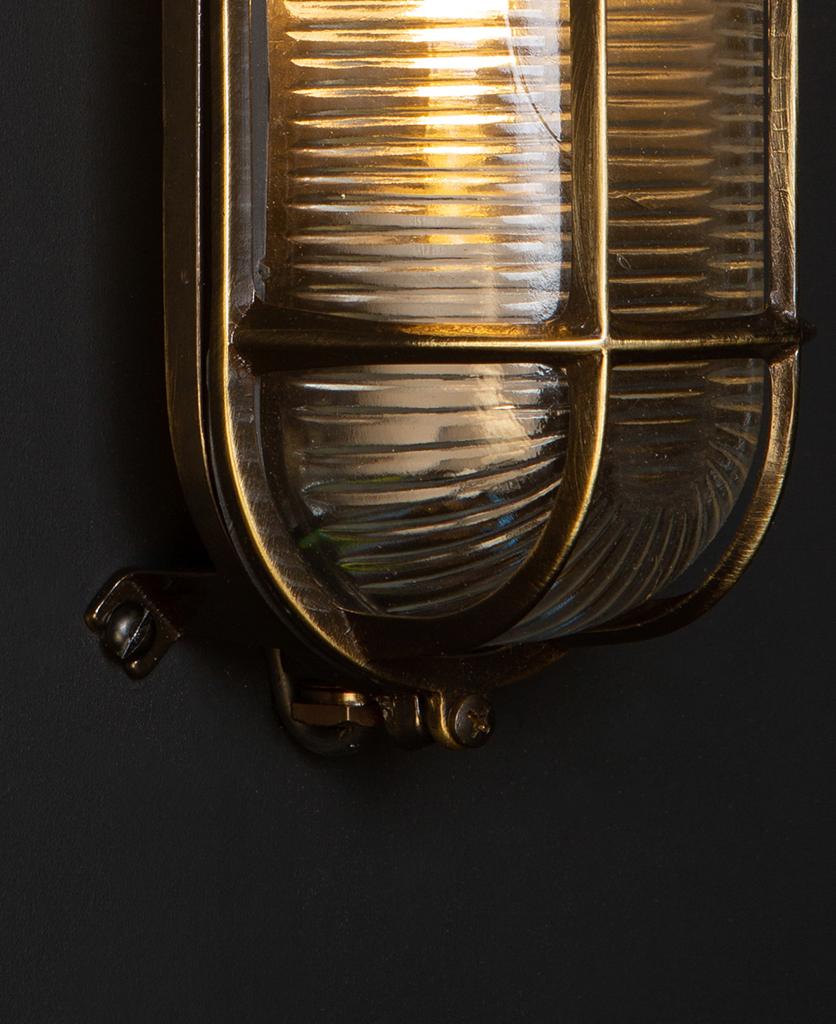 closeup of lit dave aged brass bulkhead light against black background