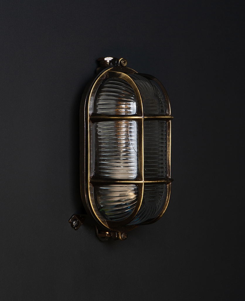 unlit dave aged brass outdoor bulkhead light against black background