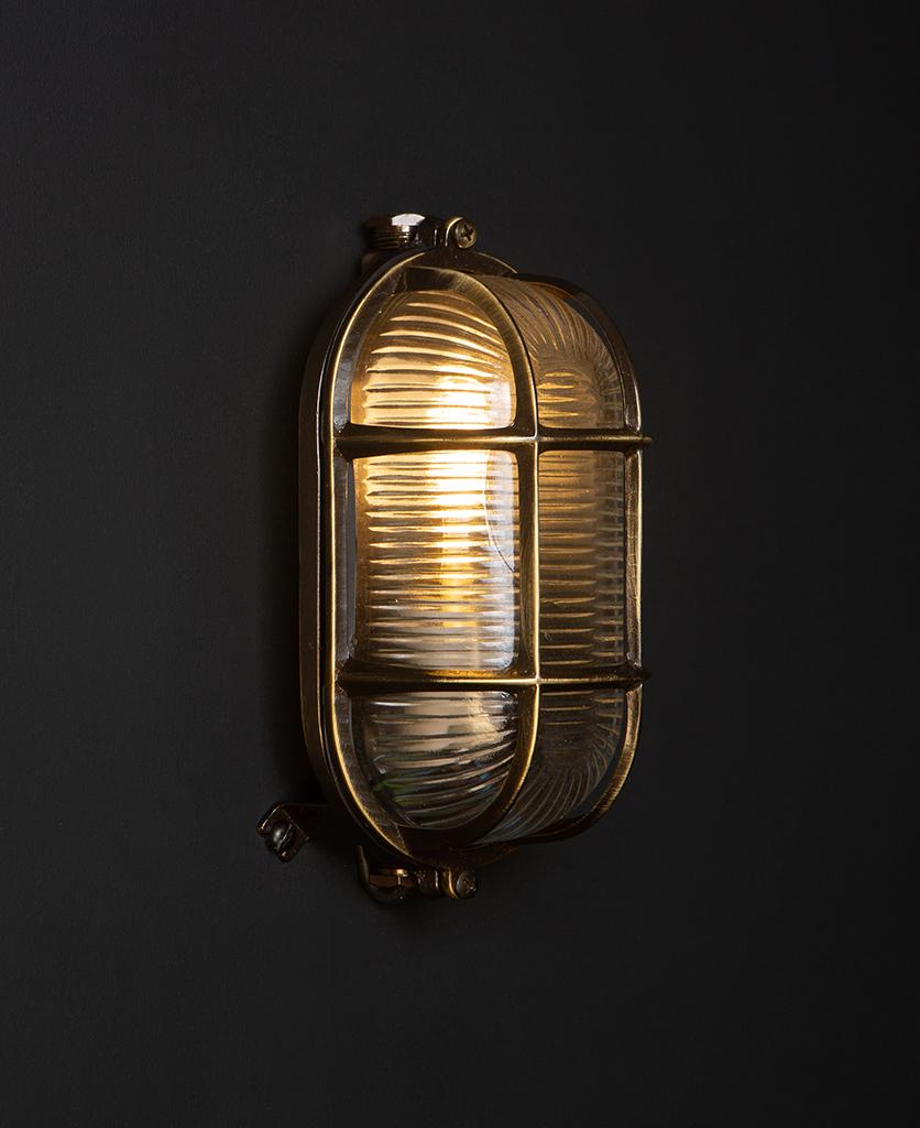 dave lit aged brass outdoor bulkhead light on black wall