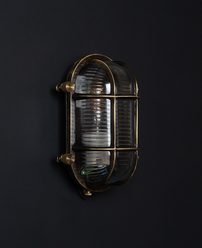 steve unlit aged brass bulbkhead light with posh knobs against black background