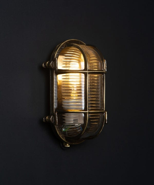 steve aged brass bulkhead outdoor lights with lit bulb against black background