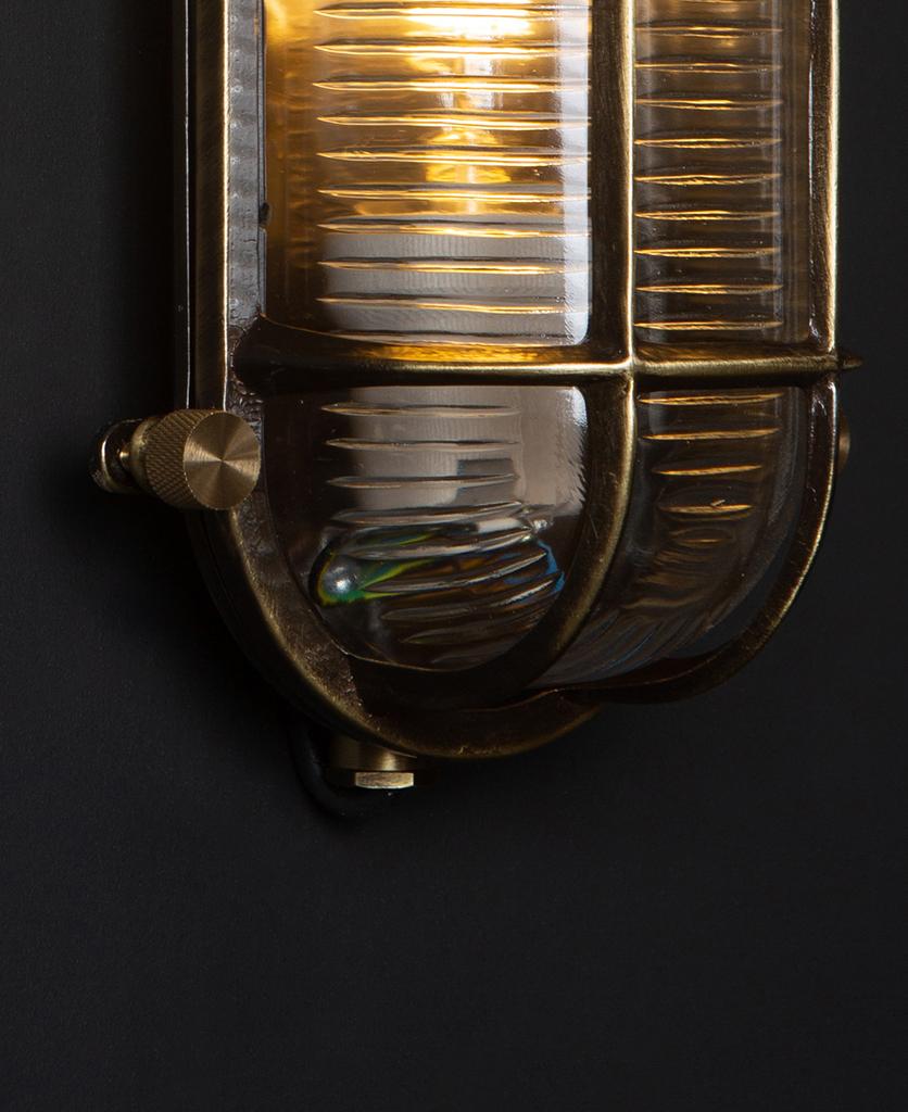 closeup of steve lit aged brass bulbkhead light with posh knobs against black background