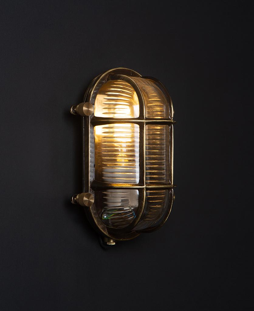 steve lit aged brass bulbkhead light with posh knobs against black background