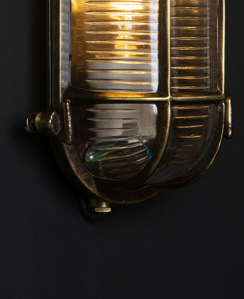 closeup of steve aged brass bulkhead outdoor lights with lit bulb against black background