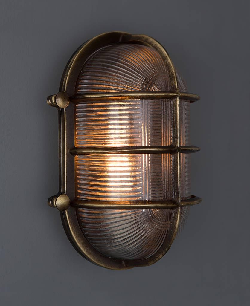lit big steve aged brass bulkhead wall light against grey wall