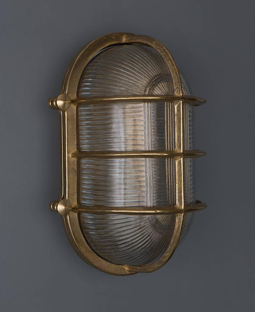 unlit big steve brass bulkhead wall light against grey wall