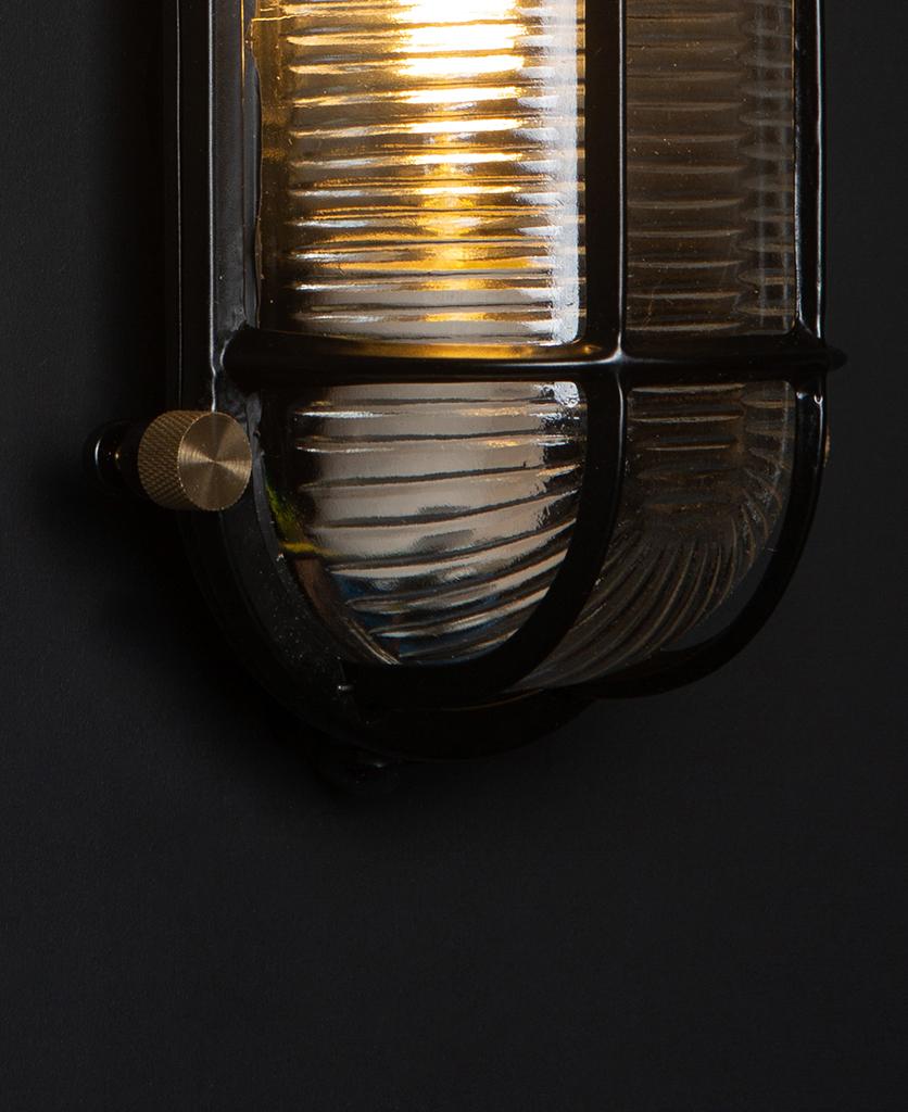closeup of steve lit black bulkhead light with posh knobs against black background