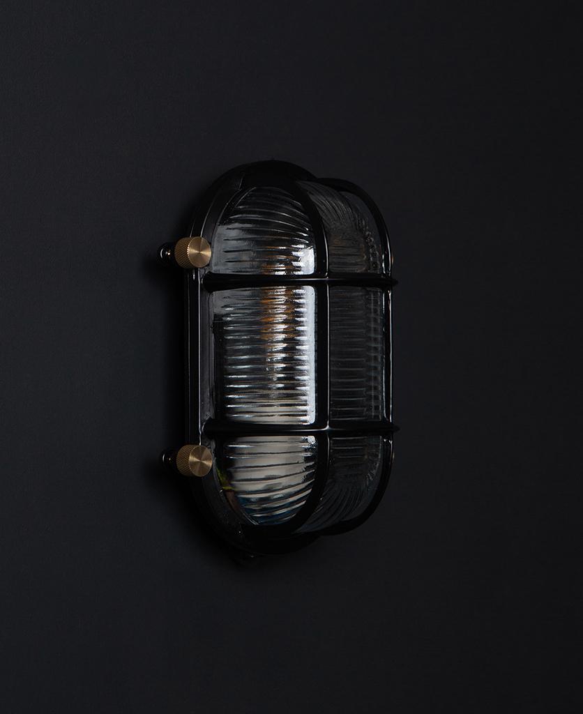 steve unlit black bulkhead light with posh knobs against black background