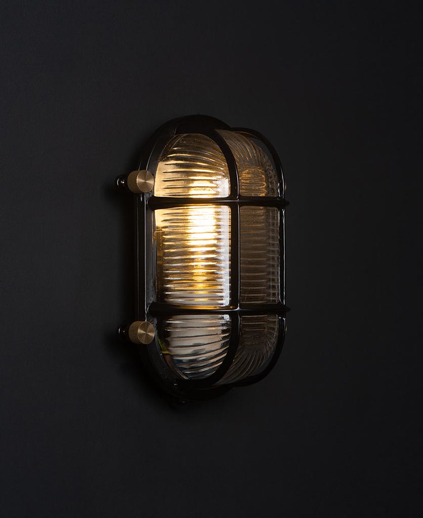 steve lit black bulkhead light with posh knobs against black background