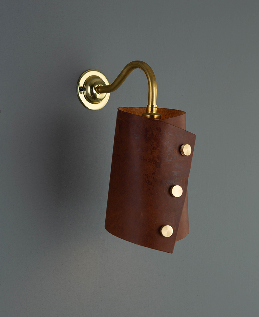 polished brass wall sconce lighting with dark tan leather light shade on grey wall