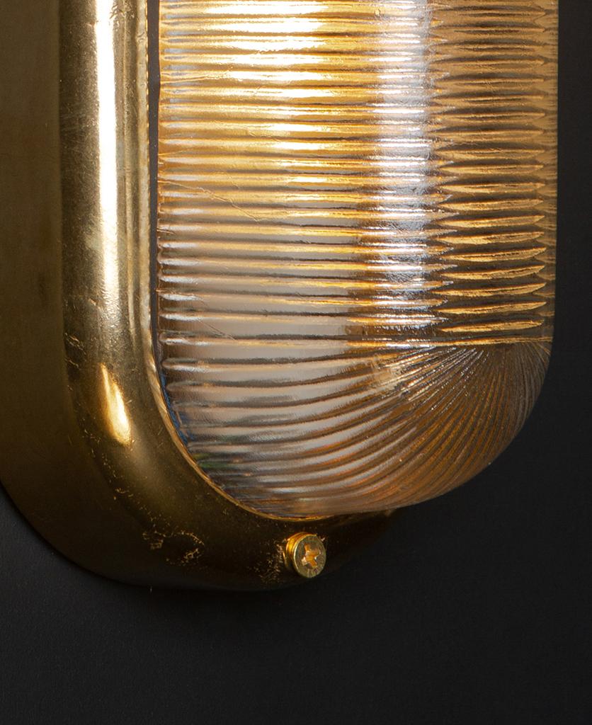 close up of lit mike brass external led bulkhead light against black background
