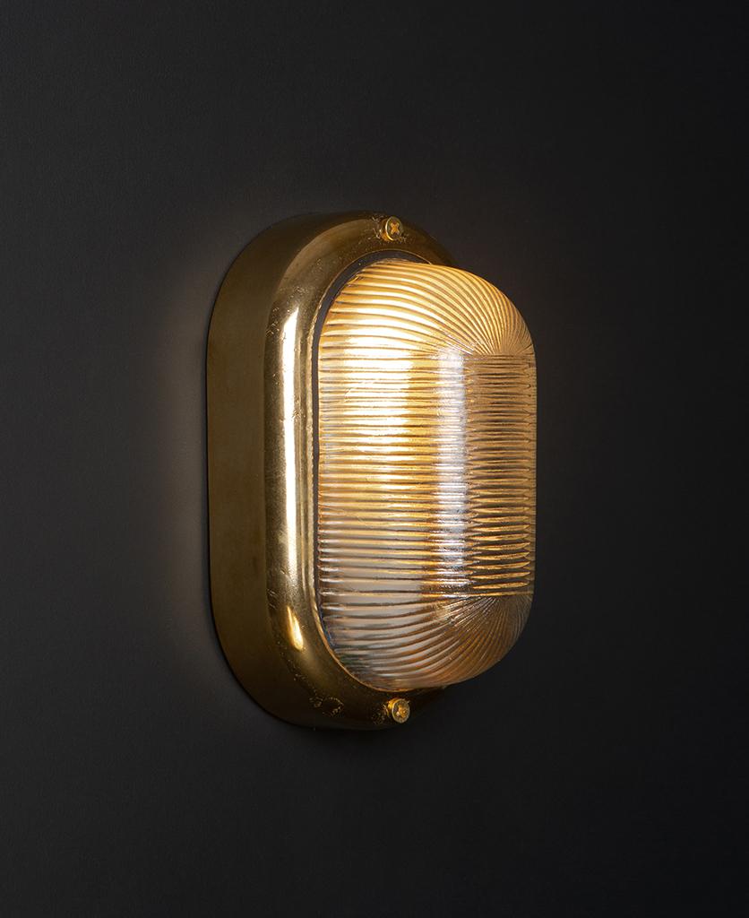 lit brass mike led external light on black wall